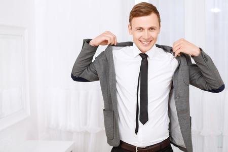 Gut fühlen. Lächelnde junge gut aussehend Mann, der auf Jacke auf weißem Hintergrund.