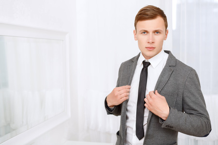 youthful: Fashion is my profession. Youthful handsome young man posing in suit on white background. Stock Photo
