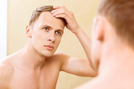 seins nus: Fourbir jusqu'à. Topless jeune homme fixant ses cheveux devant un miroir.