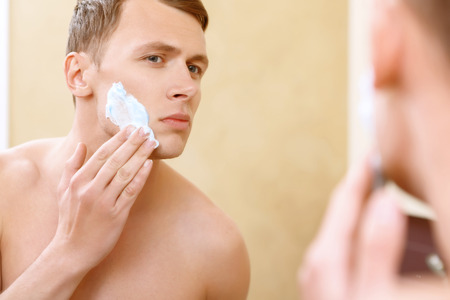topless: Doing careful. Topless man applying mean of shaving on his face in front of mirror.