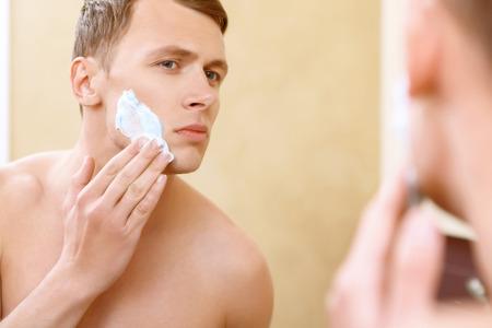 seins nus: Faire attention. homme Topless application moyenne de raser sur le visage dans le miroir. Banque d'images