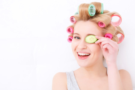 pj's: Beauty procedures. Portrait of a young beautiful blond girl sitting in the light background smiling and holding slice of cucumber near her eye while wearing pajama and colorful hair curlers Stock Photo