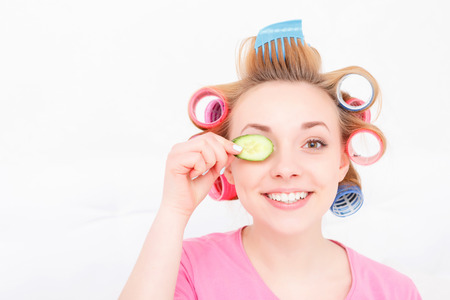 hair roller: Happy youth. Young pretty girl wearing colorful hair curlers and pink T-short holding a slice of cucumber near her eye and smiling isolated on white background