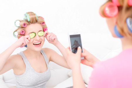 hair roller: Pajama party. Young blond girl making mobile photo of her beautiful friend laughing and holding cucumbers on her eyes wearing colorful hair curlers and grey shirt