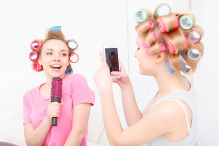 cute lady: Sing a song. Two happy young friends having fun making mobile photos and pretending singing into the hairbrush wearing pajamas and colorful hair curlers at home
