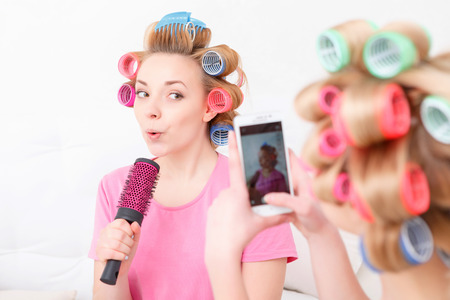 hair roller: Sing a song. Two happy young friends having fun making mobile photos and pretending singing into the hairbrush wearing pajamas and colorful hair curlers at home