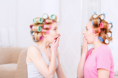 hair roller: Amazement. Two young blond girls looking at each other with their mouths opened being surprised and wearing pajamas and colorful hair rollers at home party in the light room