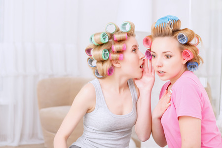 Did you know. Young blond girl sharing a secret to her best friend looking very surprised wearing pajamas and colorful hair rollers at home party in the light room