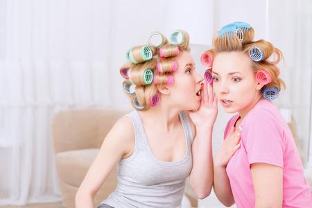 pijamada: Sabías. Muchacha rubia joven compartir un secreto a su mejor amigo que parece muy sorprendido en pijama y los rodillos del pelo de colores en el partido en casa en la sala de la luz Foto de archivo