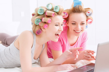 pj's: Young beautiful girls wearing pajamas and colorful hair rollers lying on the bed laughing and looking at laptop at home party in the light room Stock Photo