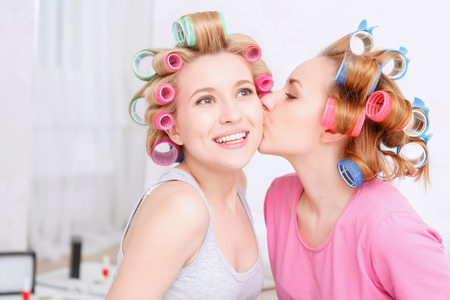 hair roller: Friendship. Young blond girl kissing her best friend at her cheek smiling and wearing pajamas and colorful hair rollers at home party in the light room Stock Photo