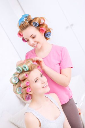 pajama party: Making wavy hair. Portrait of young beautiful girl wearing pajamas and colorful hair rollers smiling and making her friend a hairstyle at pajama party Stock Photo