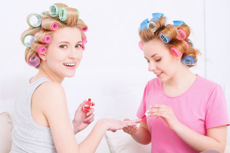 pajama party: Portrait of young girls wearing pajamas and colorful hair rollers painting nails in red color and smiling at pajama party in the light room