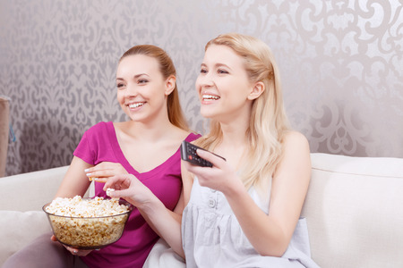 pajama party: Movie night. Two young beautiful girls sitting on a white couch watching a movie while holding remote control and eating popcorn at pajama party full length