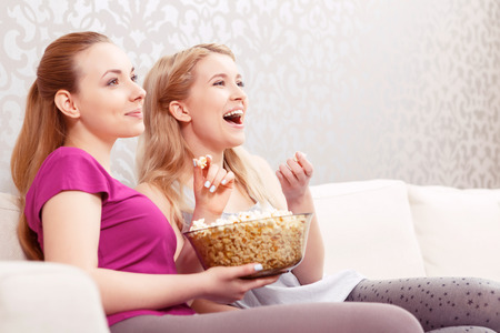 eating popcorn: Comedy movie. Two young beautiful girls sitting on a white couch watching a movie and laughing while eating popcorn at pajama party side view Stock Photo