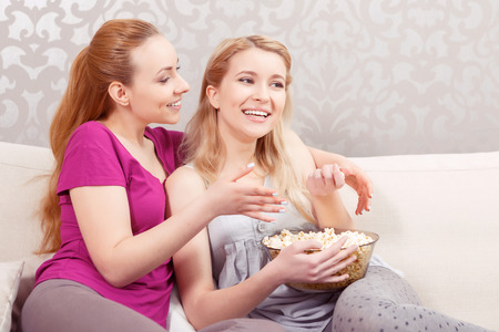 pajama party: Comedy movie. Two young beautiful girls sitting on a white couch watching a movie and hugging each other while eating popcorn at pajama party side view