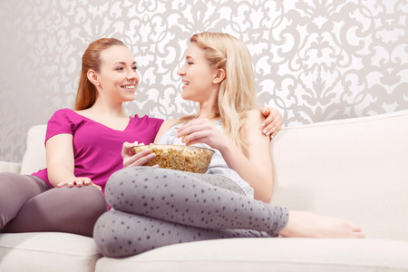 pj's: Movie night. Two young beautiful girls sitting on a white couch hugging and discussing a movie while eating popcorn at pajama party full length
