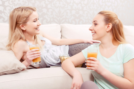pjs: Girls night in. Beautiful young girl lying on a white couch drinking juice and laughing while her friend sitting on the floor next to her at pajama party Stock Photo
