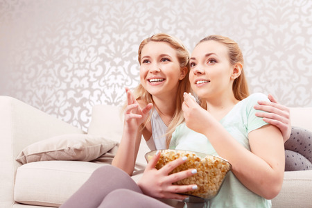 pajama party: Girls night in. Beautiful young girl lying on a white couch pointing at the tv screen hugging her friend sitting on the floor next to her at pajama party Stock Photo