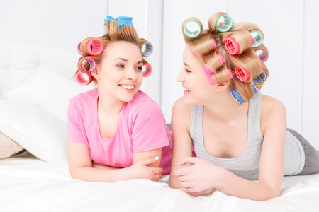 hair roller: Slumber party. Two young beautiful blond girls wearing pajamas and colorful hair rollers sitting in white bed smiling and looking at each other