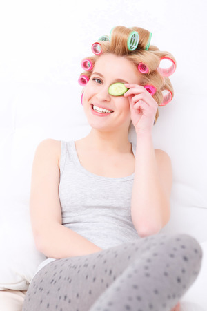 hair roller: Beauty procedures. Portrait of a young beautiful blond girl sitting in the light background smiling and holding slice of cucumber near her eye while wearing pajama and colorful hair curlers Stock Photo