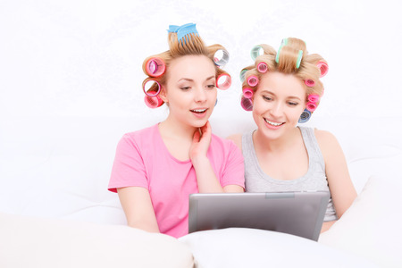 hair roller: Slumber party. Two young beautiful blond girls wearing pajamas and colorful hair rollers sitting in white bed and looking at the tablet smiling Stock Photo