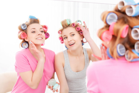 Slumber party. Two young beautiful blond girls wearing pajamas and colorful hair rollers standing near the mirror and using face cream and correcting the hair curlers view from the back photo