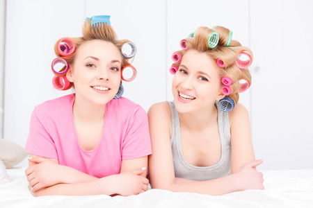 hair roller: Slumber party. Two young beautiful blond girls wearing pajamas and colorful hair rollers lying at white bed smiling and looking at the camera Stock Photo