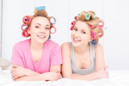soir�e pyjama: Soir�e pyjama. Deux belles jeunes filles blondes pyjama et galets color�s de cheveux se trouvant au lit blanc souriant et en regardant la cam�ra