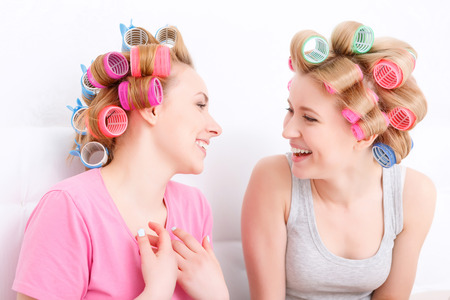 slumber: Slumber party. Two young beautiful blond girls wearing pajamas and colorful hair rollers sitting in white bed smiling and looking at each other