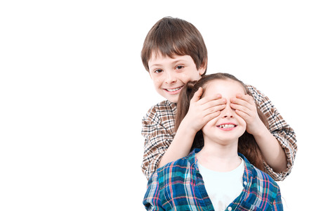 guess: Guess who. Small handsome boy standing behind his little pretty sister and playfully closing her eyes while she is smiling isolated on white background