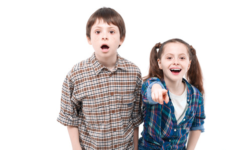 mouth opened: Look at this. Small pretty girl standing next to her older brother and pointing at you with her finger while her brother looking that way surprised with his mouth opened isolated on white background