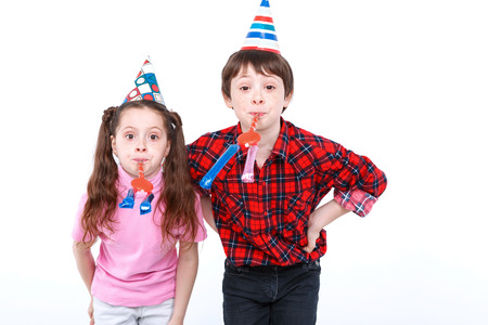 arms akimbo: Party time. Small handsome boy and his little pretty sister wearing cone caps standing near holding arms akimbo caps and blowing into party horns, isolated on white background Stock Photo