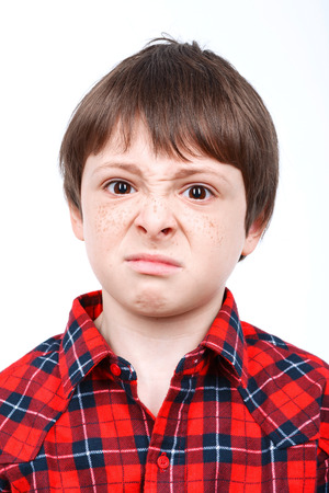 unsatisfied: Portrait of a small boy looking very unsatisfied wearing checkered shirt close up isolated on white background