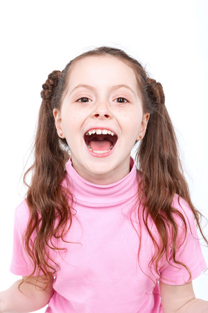 mouth opened: Portrait of a small girl looking very happy laughing with her mouth opened wearing pink turtleneck isolated on white background Stock Photo