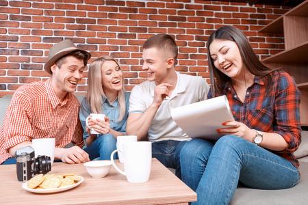 grupo de hombres: Reunión feliz. Muchacha sonriente joven escribiendo en un cuaderno mientras que su amiga riendo hablando de algo de beber divertida de té, galletas y tazas de la cámara en la mesa