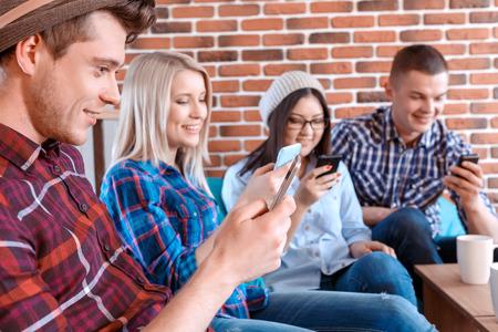 personas sentadas: Smartphones gobiernan el mundo. Chico guapo joven y sus amigos sentados en un caf�. Todo el uso de sus tel�fonos m�viles en vez de hablar el uno al otro enfoque selectivo Foto de archivo