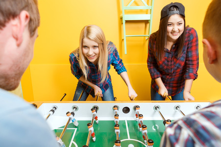 foxy girls: Boys vs girls. Young happy friends absorbedly playing table hockey two girls against two boys in a yellow room while a blond girl looking foxy selective focus