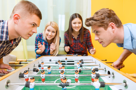 bend over: Big play. Two young boys standing bend over a hockey table looking challenging at each other trying to win a match while their girlfriends cheering them up