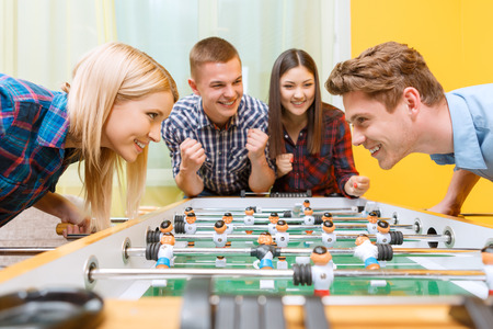 hockey: Lets play. Beautiful young blond girl looking smiling at her partner while playing air hockey wearing checkered shirt in a yellow room, while friends cheering them up Stock Photo