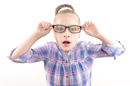 mouth opened: Portrait of a small pretty girl wearing reading glasses touching black spectacle frame with her hands looking surprised with her mouth opened ,wearing colorful checkered shirt
