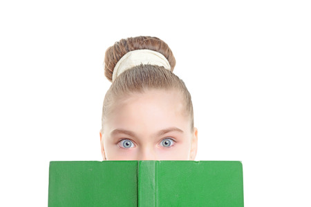 eyes wide: Portrait of a small girl hiding behind a green book looking with her eyes wide opened with big bun hairstyle isolated on a white background, close up Stock Photo