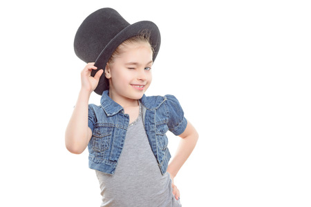 Portrait of a small pretty girl holding a big top hat on her head and giving a wink with a foxy look wearing a grey t-shirt and jeans jerkin, isolated on a white background 版權商用圖片