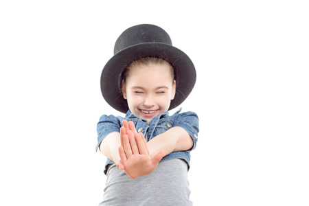 big top: Portrait of a small pretty girl with a big top hat on her head laughing with eyes closed and holding her hands in front of her wearing and jeans jerkin ,isolated on a white background ,selective focus
