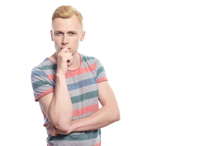 youthful: Thinking concentrated. Handsome youthful blond man standing with crossed arms and holding his hand on chin area on isolated white background
