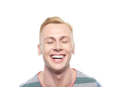 Mort de rire. Attractive jeune homme blond souriant sur fond blanc isolé
