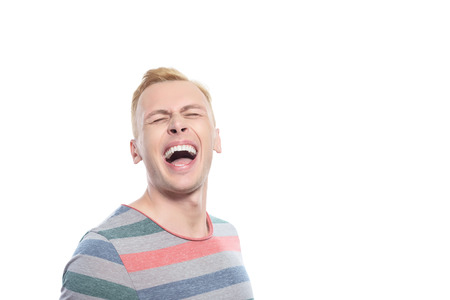 youthful: Laughing hard. Handsome youthful blond man laughing on isolated white background