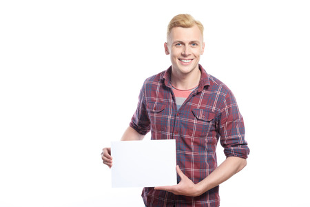 glance: Pure glance. Smiling handsome man holding white sheet of paper on his waist area against isolated background. Stock Photo