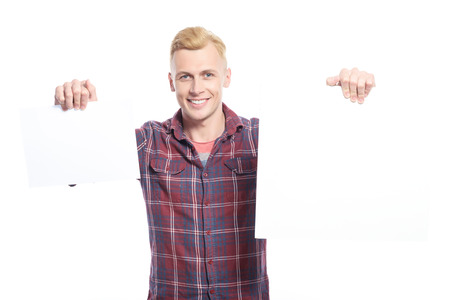youthful: In both hands. Youthful handsome smiling blond man holding two white sheets of paper against isolated background