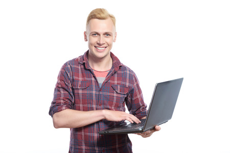 lap top: Using technologies. Youthful handsome blond man standing with lap top against isolated background